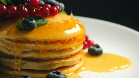 frenk üzümü : Stack of fresh fluffy pancakes decorated on top with forest berries rotating on plate and pouring honey syrup. Delicious, healthy american breakfast. Fresh bakery concept. Stok Video