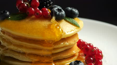 креп : Stack of fresh fluffy pancakes decorated on top with forest berries rotating on plate and pouring honey syrup. Delicious, healthy american breakfast. Fresh bakery concept. Стоковые видеозаписи