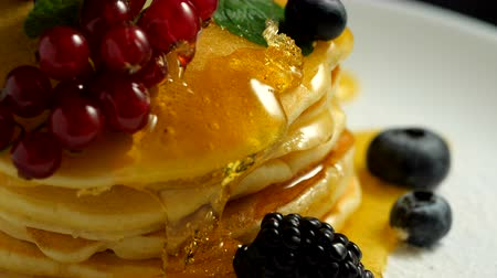 american cuisine : Stack of homemade pancakes or crepes decorated on top with forest berries - red currant and blueberry. Delicious, healthy classic american breakfast. Close-up Stock Footage