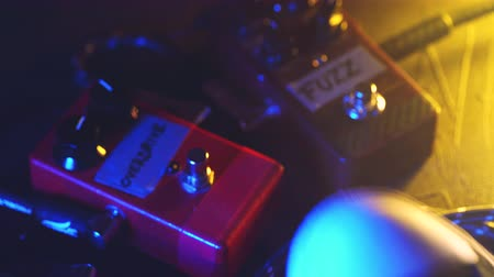 rocker : Close up of guitar player or rock musician playing overdrive and fuzz pedal on his show. Mans foot pressing on metal button for different sounds. Macro view. Neon light.