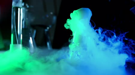 dioxid : Flask with colorful liquid are steaming in neon light. Beautiful chemical reaction with dry ice in water. The concept of chemistry tests demonstration and experiments. Edutainment Stock mozgókép