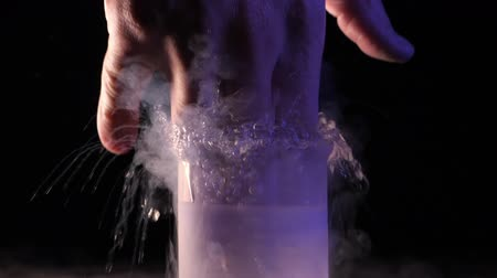 banka : Man puts his hand in container with liquid nitrogen. Concept of chemical experiments and tests. Edutainment. slow motion