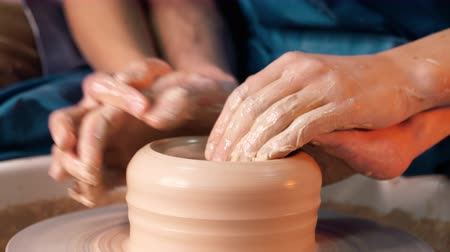 oleiro : Hands of young couple in love making clay jug on potters wheel. Sensual footage of people on romantic date. Pottery training, artwork concept.