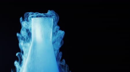 kırılganlık : Cold blue flask with liquid nitrogen on black background. Concept of chemical experiments and tests. Edutainment. Copy space. 4k. Stok Video