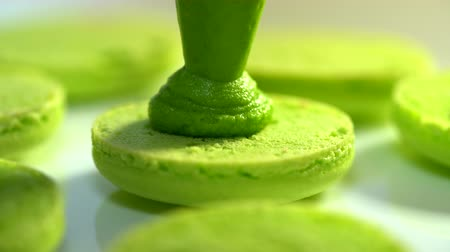 macarons : Making green pistachio macarons, squeezing and adding cream filling from pastry bag. Macaroons - delicious and beautiful french dessert. Cooking, food and baking, pastry concept.