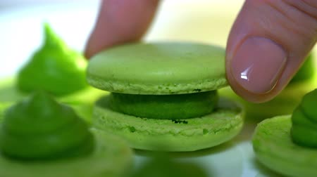 macarons : Chef connecting two halves of green pistachio macaroons with cream. Macarons - delicious and beautiful french dessert. Cooking, food and baking, pastry shop concept. 4k Stock Footage