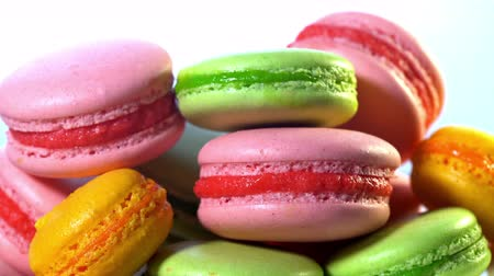 macarons : French macarons - meringue cookies with ganache or buttercream filling. Colorful macaroons rotating, horizontal view , slow motion. Cooking, food and baking, pastry shop concept. Stock Footage
