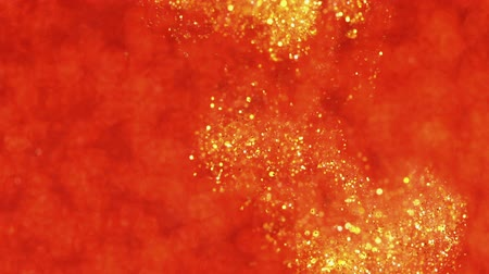 limpar : Gold ink in water on red. Glitter paint reacting creating abstract cloud formations. Shining sparkles. Can be used as transitions,added to modern projects,art backgrounds.