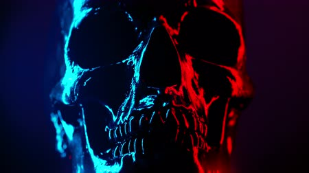 kanlı : Ancient human skull head rotating close-up. Neon turquoise and red light. Spooky and sinister. Glamour, disco, halloween concept.
