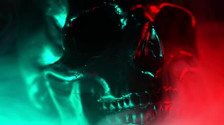 arkeolojik : Shining skull head rotates from left to right on dark smoke background with neon red and green light. Halloween celebration, glamour, style concept. fear and horror