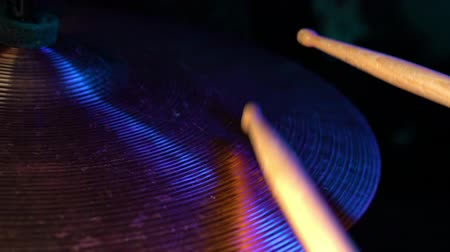 cymbals : Drumsticks hits on crash cymbals close up. Side view, Neon pink and blue colorful light. Slow motion. Music concept Stock Footage