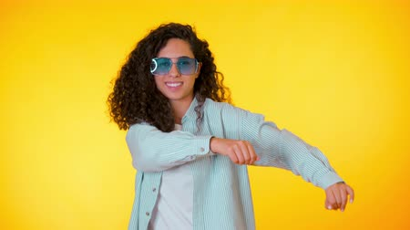 teljes hosszúságú : Female having fun. She smiling, hair flutter beautifully. Amazing positive footage. Girl moves to the rhythm of music. Woamn with curly hair dancing on yellow background. Stock mozgókép