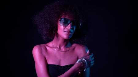 peruka : Portrait of young sexy african girl with blue glasses in pink neon light at black background. Woman with perfect makeup looking at camera and smiling. Glamour, fashion concept Wideo