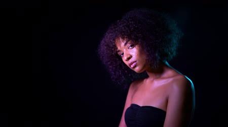 peruka : Portrait of young seductive african american girl in pink neon light at black background. Tempting woman with perfect makeup looking at camera and smiling. Glamour, fashion concept.