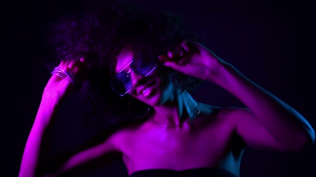seductive : Tempting woman with perfect make-up smiling, enjoying moment, music. Young african girl with curly hair dancing in neon light. Glamour, fashion, style concept. Stock Footage