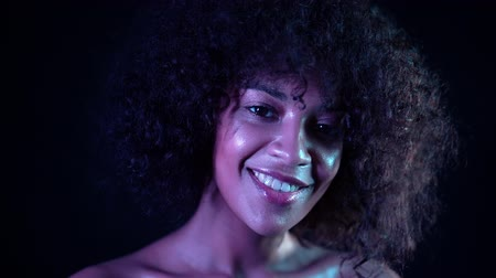 peruka : Portrait of young mixed race girl. Healthy skin concept. Positive cute woman with make-up posing in dark room on black background. Wideo