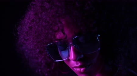 peruka : Portrait of young mulatto girl in violet neon light. Fashion, glamour, model concept. Seductive woman with make-up and transparent glasses posing in dark room at night.