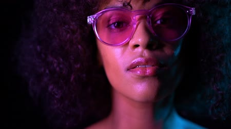 peruca : Portrait of young alluring mixed race girl in neon light. Fashion, glamour, model concept. Seductive woman with make-up and transparent glasses posing in dark room at night