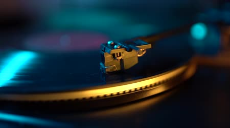retro revival : Cinemagraph loop vinyl record player turntable with its stylus running along music plate. Neon light. Retro-styled spinning record vinyl player. Close up
