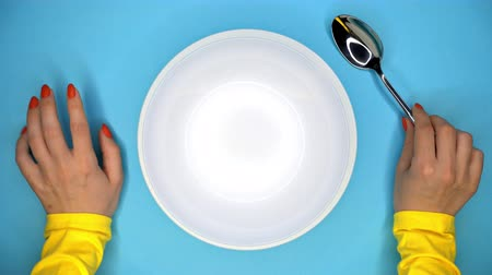 příbory : Hands of young woman with spoon. Lady sitting in restaurant and waiting for order. Girl knocks fingers nervously on the table while waiting for her dish. Empty white plate on blue background