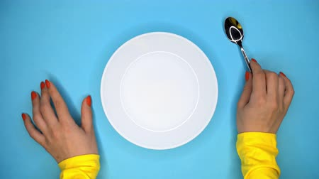 столовая : Hands of young woman with spoon. Lady sitting in restaurant and waiting for order. Girl knocks fingers nervously on the table while waiting for her dish. Empty white plate on blue background