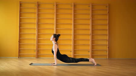 meditující : Surya Namaskar. Woman in black bodysuit doing yoga practice in yellow studio on stairs background. Health, lifestyle, sports concept Dostupné videozáznamy