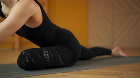 beyin : Unrecognizable woman indoors in yellow class space doing stretching legs in sitting position. Young woman in black practicing yoga at light minimalist studio.