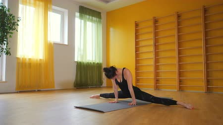 分割 : Young woman in black practicing stretching, fitness or yoga alone in minimalist yellow studio. Girl doing split cross twine. Health lifestyle concept 動画素材