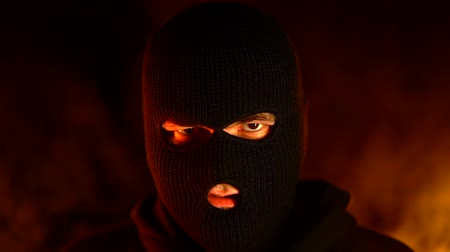 balaclava : Portrait of young man in black balaclava against backdrop of a blazing night fire. Concept of mass rallies and riots Stock Footage