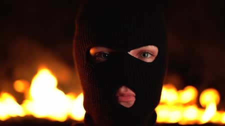 gengszter : Portrait of young woman ultras or protester in black mask against backdrop of blazing night fire. Concept of mass rallies and riots