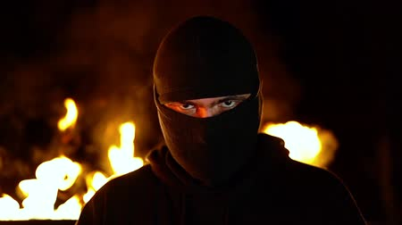 commando : Portrait of protesting activist in mask against burning barricades at night. Concept of strikes, political conflicts and confrontation.