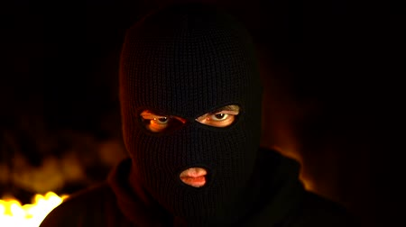 intruder : Portrait of protesting activist in black balaclava against burning barricades at night. Concept of strikes, political conflicts and confrontation
