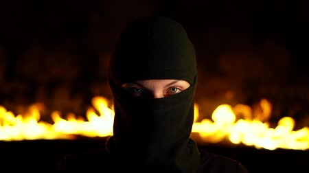 overval : Portrait of female protesting activist in black balaclava against burning barricades at night. Concept of strikes, political conflicts and confrontation.
