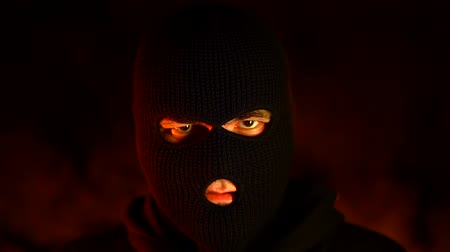 intruder : Portrait of young man in black mask during street fights against burning fire background. Concept of political strikes and football hooligans - ultras.