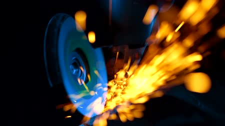 locksmith : Close-up of worker at construction plant saws metal using circular saw. Industrial production, locksmith industry concept . Sparks from grinding wheel. Stock Footage