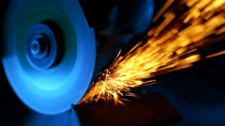 hasznosság : Close-up of welder grinding smooths steel and iron using modern equipment. Industrial production, locksmith industry concept. Sparks from grinding wheel. Stock mozgókép