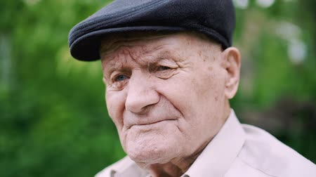 smutny : Very old caucasian man portrait. Grandfather is sad. Portrait: aged, elderly, loneliness, senior with lot of wrinkles on face. Close-up of a pensive old man sitting alone outdoors.