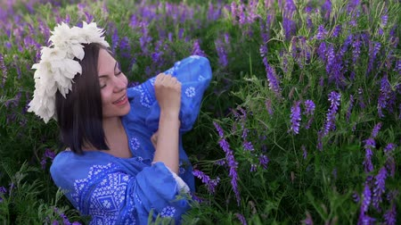 krans : Young pretty woman with flower wreath dancing in purple field. Girl in blue clothing having fun.