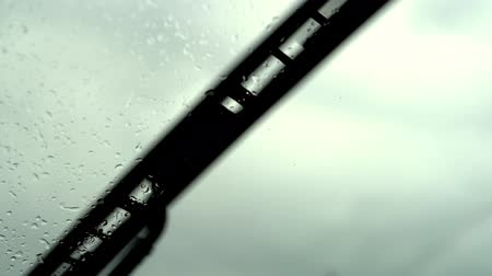 мрачный : Windshield with raindrops wiped by automobile wipers. Rainy, stormy weather. Стоковые видеозаписи
