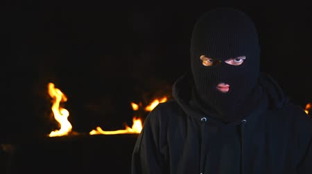 balaclava : Portrait of protesting activist in mask against burning barricades at night.