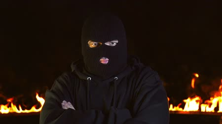 balaclava : Portrait of man in balaclava shows head affirmative gesture against blazing fire
