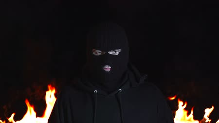 balaclava : Portrait of young man in black balaclava against backdrop of blazing night fire