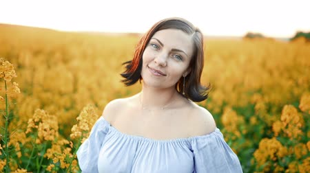 kolza tohumu : Portrait of young pretty woman in blue dress posing in rapeseed yellow flowers field. Spring time, sunset light.