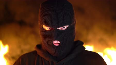 combustão : Portrait of young man in black mask during street fights against burning fire background. Concept of political strikes and football hooligans - ultras