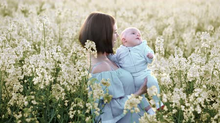kolza tohumu : Portrait of young mother with newborn son having fun in yellow field. Love, family, joy concept.