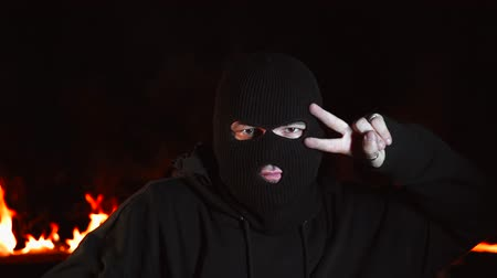 balaclava : Portrait of dancing  ultras man in balaclava against of blazing night fire Stock Footage