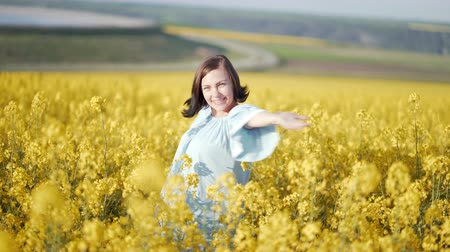 open blossom : Portrait of happy woman in blue dress unexpectedly pops up with open arms among yellow canola flowers in field