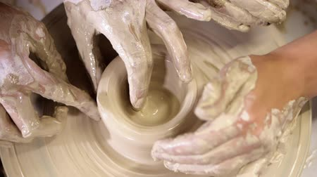 oleiro : Hands of young couple in love making clay jug on potters wheel.