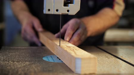 резать : Joiner labourer cuts wooden plank on jigsaw machine. Carpenter working in workshop. Handwork, carpentry concept, woodworking.