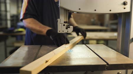 lumber : Joiner working in studio. Woodworker cuts wooden plank on jigsaw machine. Handwork, carpentry concept, woodworking.